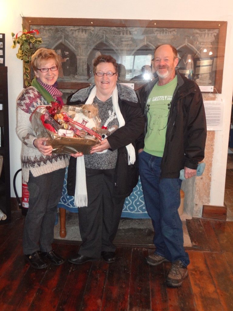 Mrs Christine Wellman, accompanied by her husband Eddy, receives her Christmas hamper prize from Jacqueline McCullogh, a member of the Colyton Parish History Society.